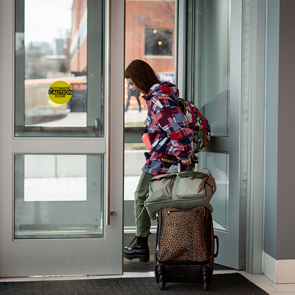 Student pulling suitcase through door